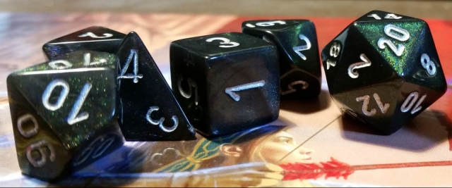 A set of D&D dice on top of a folded DM screen. Image credit: Pixabay.