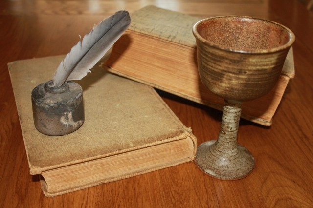 A table on which a goblet, two books and a quill pen and inkwell are arranged. Image credit: Pixabay.