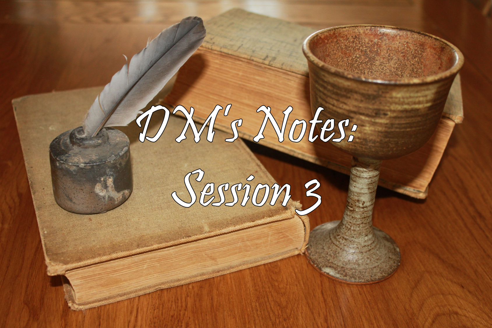 A wooden tabletop, on top of which are two books, a goblet and a quill pen and inkwell. Text: 'DM's Notes: Session 3'. Image credit: Pixabay.